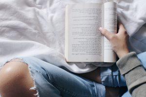 Frau liest mit Löchern in der Hose kl_XvEOqMU-unsplash